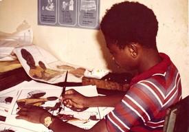 Een schooljongen kleurt de tekeningen in